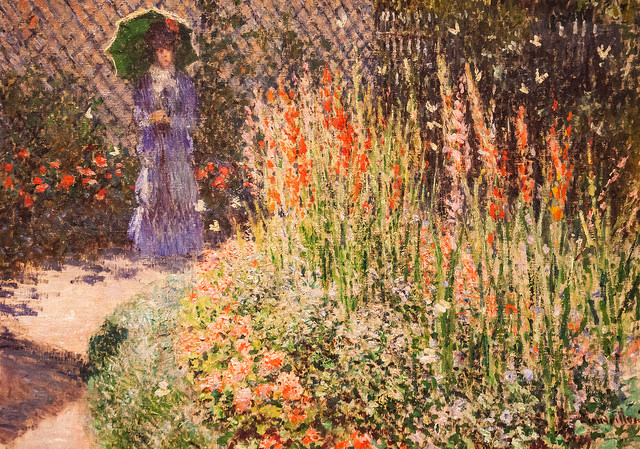 Woman in garden of Gladioli. Gladioli symbolize strength.